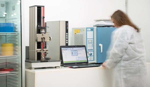 Técnicos especialistas durante el proceso de laminación de productos adhesivos en la planta de laminado Fustier